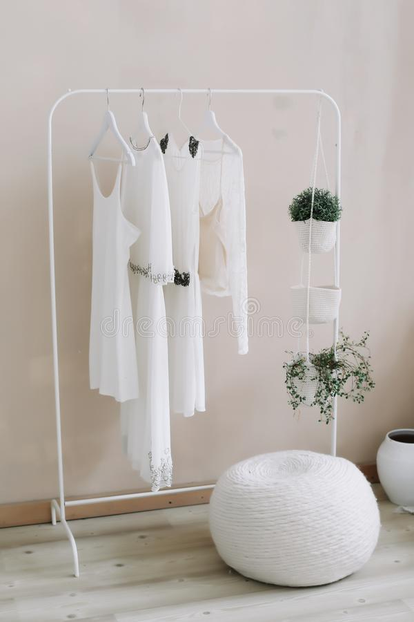 Vita klänningar på en hängare Minimalismbegrepp Ställ upp in av kvinnabröllopsklänningar på trähängare, modebakgrund, slut royaltyfria bilder