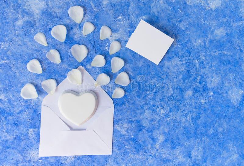 Vita kronblad av en ros ska ta av från ett öppet kuvert och en porslinhjärta En mall för ett kort Kopieringssp royaltyfri fotografi