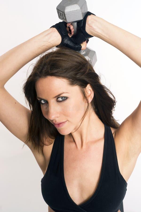 Vita krullande skivstånger för attraktiv brunettkvinna royaltyfri fotografi