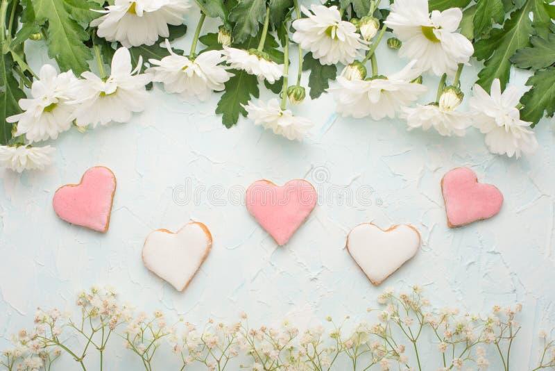 Vita krysantemum på en träbakgrund och hemlagade kakor i form av hjärtor fotografering för bildbyråer