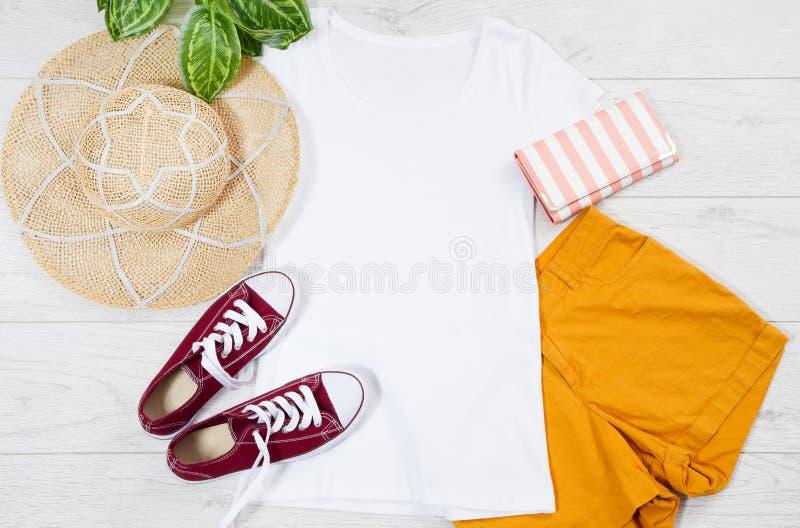 Vita kvinnliga den falska t-skjortan upp lägger framlänges på träbakgrund Utrymme f?r b?sta sikt och kopierings Modellt-skjorta o royaltyfri foto
