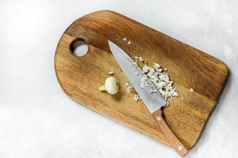 Vita lökar klippte med en kniv på ett träbräde fotografering för bildbyråer