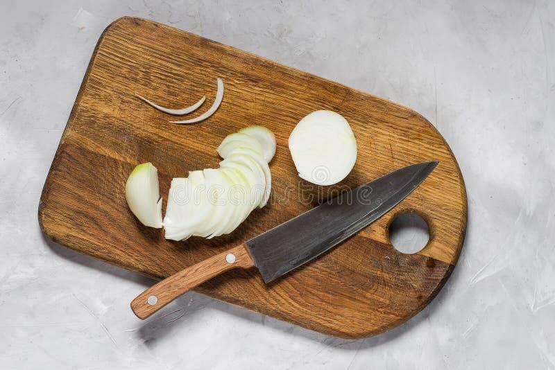 Vita lökar klippte med en kniv på ett träbräde arkivfoto