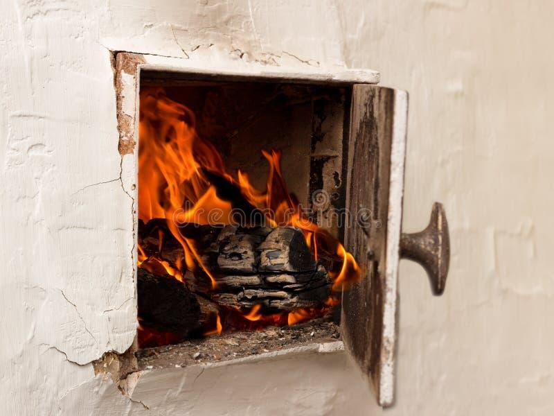 Vita lantliga ugnar för öppen dörr, brinnande trä och brand arkivbilder
