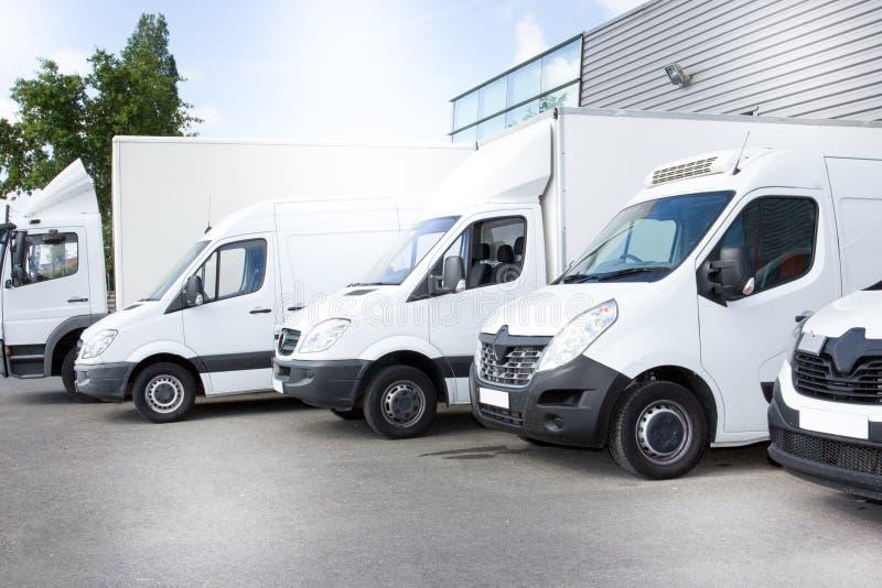Vita leveransskåpbilar åker lastbil på att parkera framme på ingången ett lager på fördelningsskåpbilen royaltyfria foton