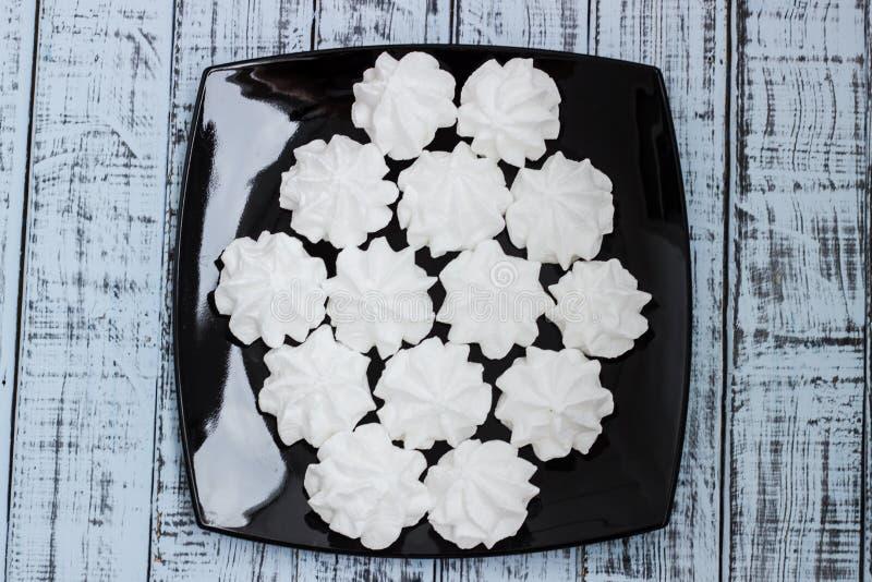 Vita marängkakor på en platta arkivbilder