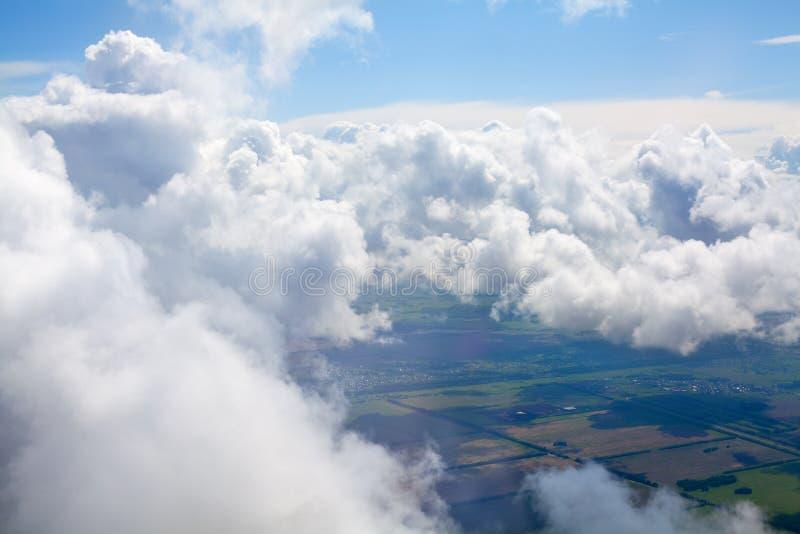 Vita moln på bakgrund för blå himmel ovanför grönt land, stackmolnmoln som är höga i himlar, härlig molnig landskapsikt från nivå arkivfoto