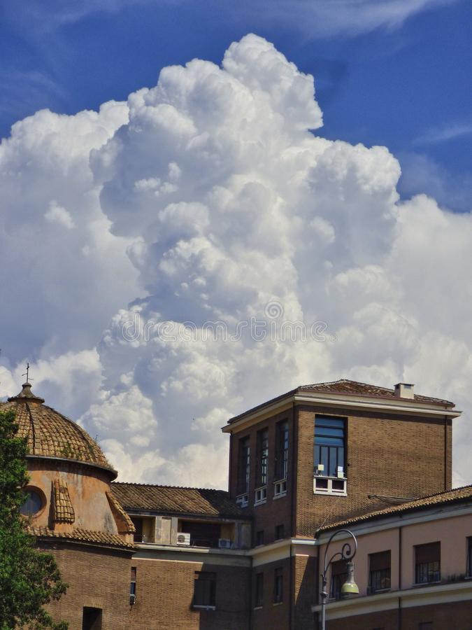 Vita moln som böljer upp bak byggnader i Rome Italien arkivfoton