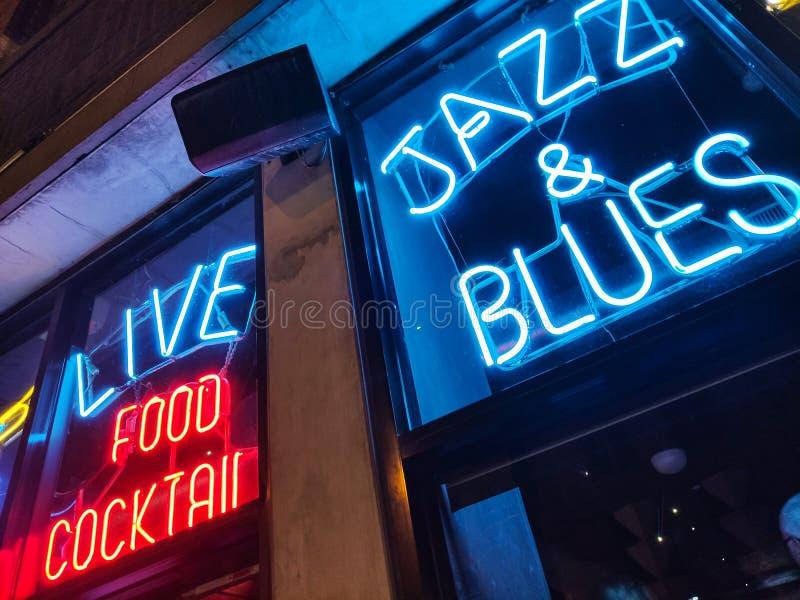 Vita notturna in Chicago con musica dei blu e di jazz Retro barra con l'insegna al neon blu e rossa fotografia stock