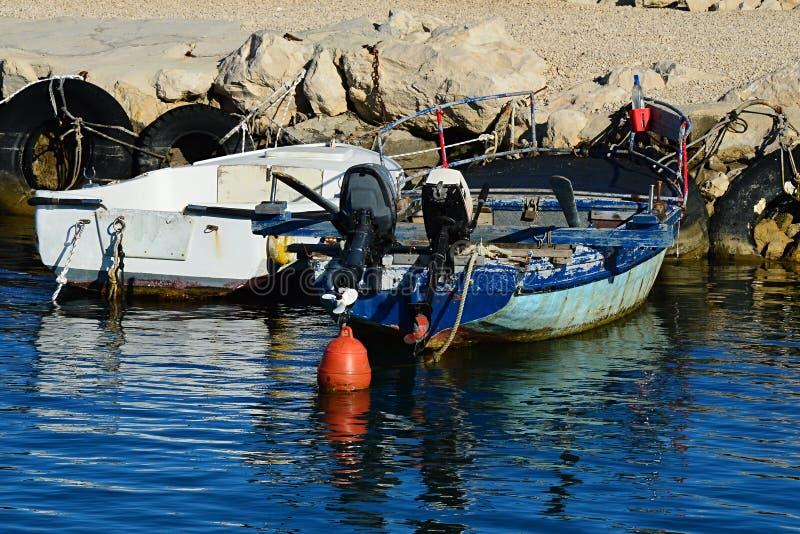 Vita och blåa fiskebåtar som binds till den steniga moloen med gamla gummihjul som stötdämpare Blått en har två motorer och den r fotografering för bildbyråer