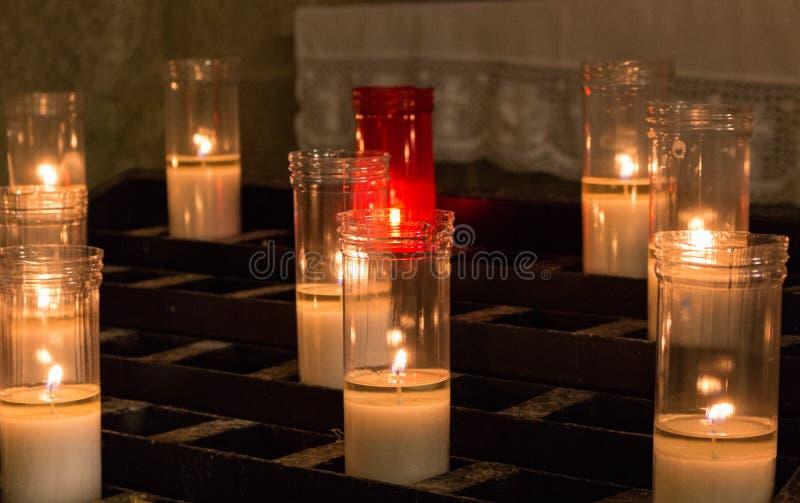 Vita och röda stearinljus i kyrka Glödande stearinljus med bränningflamman Tro- och religionbegrepp Kyrklig garnering arkivfoton