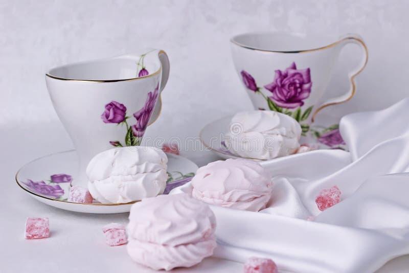 Vita och rosa marshmallower är på tabellen med härliga koppar för te royaltyfri foto