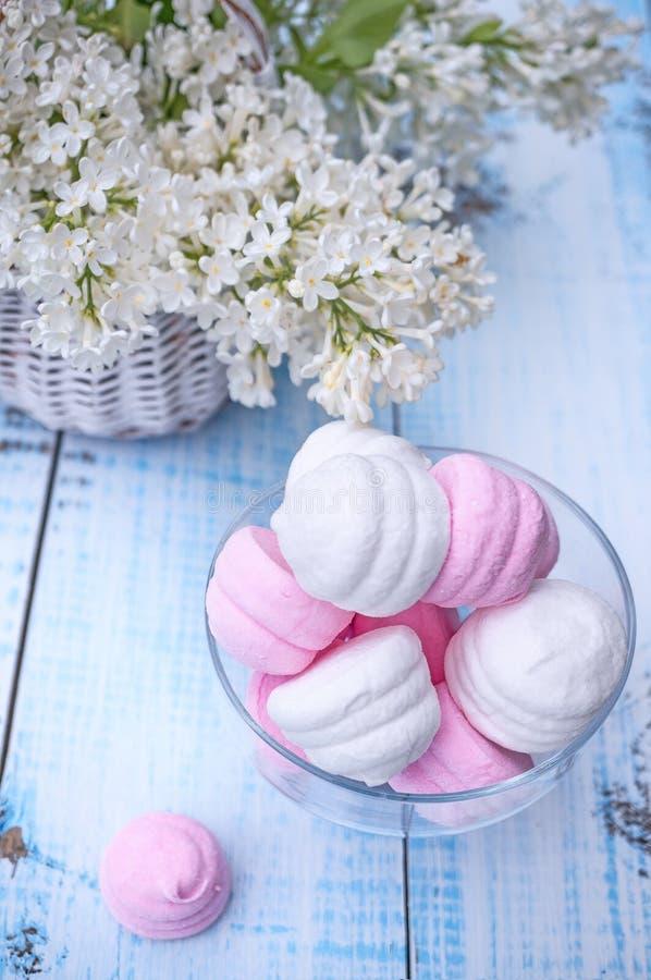 Vita och rosa marshmallower i rund glass vas med en korg av den delikata vita lilan royaltyfria bilder