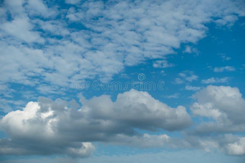 Vita och svarta moln på en ljusblå himmel arkivbild
