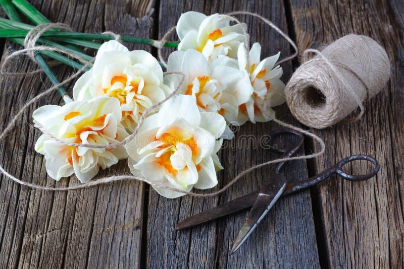 Vita påskliljablommor på gammal wood tabellbakgrund arkivfoto