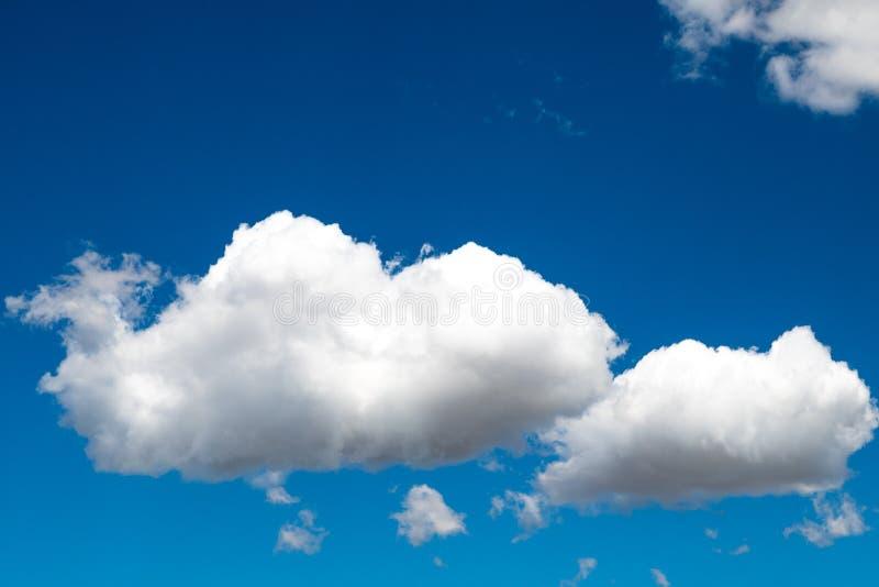 Vita pösiga moln på blå himmel arkivbilder