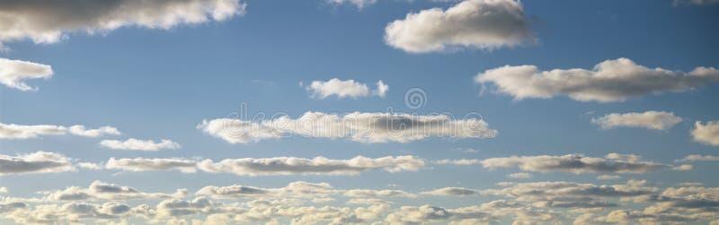 Vita pösiga oklarheter och blå sky arkivfoto