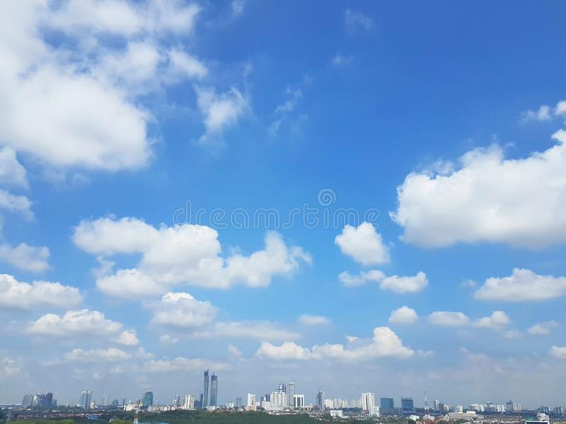 Vita pösiga stackmolnmoln över cityscape med blåa himlar royaltyfria foton