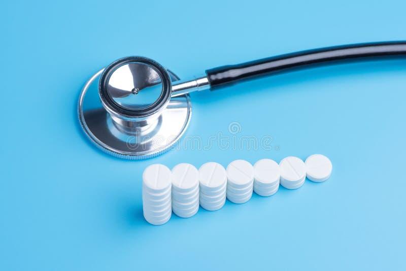 Vita piller eller minnestavlor som staplas på de i form av moment och stetoskopet royaltyfria foton
