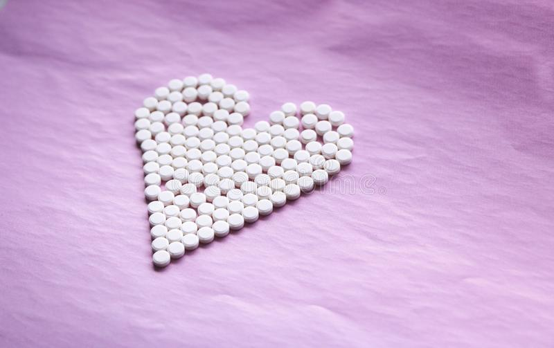 Vita piller lade ut i formen av en hjärta på en rosa bakgrund begrepp - hjärtsjukdom, hjärtaoordningar och droger, kardiologi arkivfoto