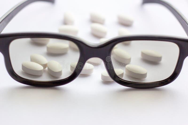 Vita piller och minnestavlor med exponeringsglas på ljus bakgrund Apotek och medicin för ögonbegrepp arkivbilder