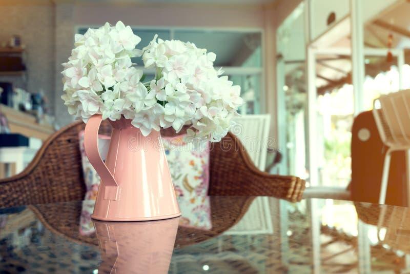 Vita plast- blommor i rosa blommavas på rottingen väver royaltyfria bilder