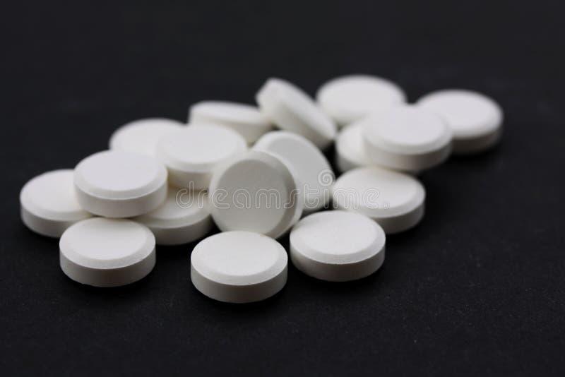 Vita preventivpillerar i ett högslut upp på svart arkivfoton