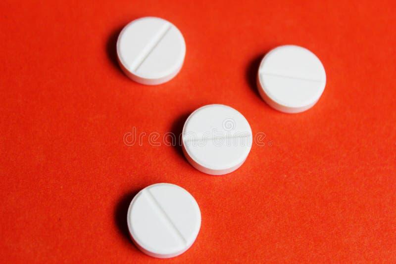 vita preventivpillerar på den orange bakgrunden arkivfoto
