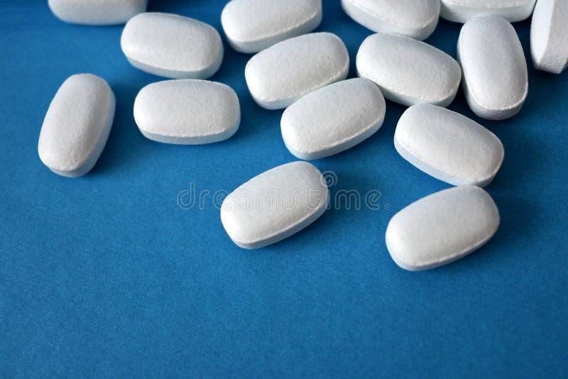 Vita preventivpillerar på en blå bakgrund royaltyfri fotografi