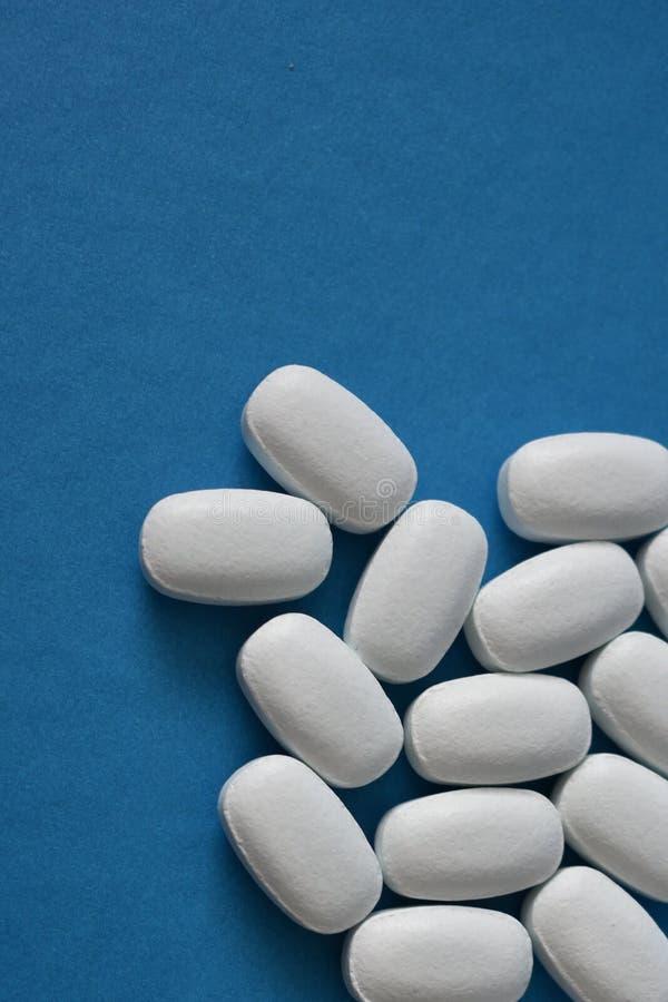 Vita preventivpillerar på en blå bakgrund arkivbild
