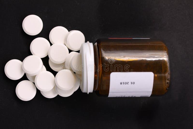 Vita preventivpillerar som spills från den stupade preventivpillerflaskan Preventivpillerar och medicinbehållare som ligger på sv royaltyfria bilder