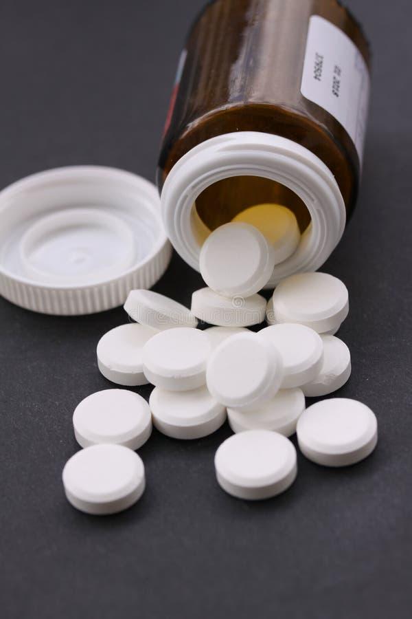 Vita preventivpillerar som spills från den stupade preventivpillerflaskan Preventivpillerar och medicinbehållare som ligger på sv royaltyfri fotografi