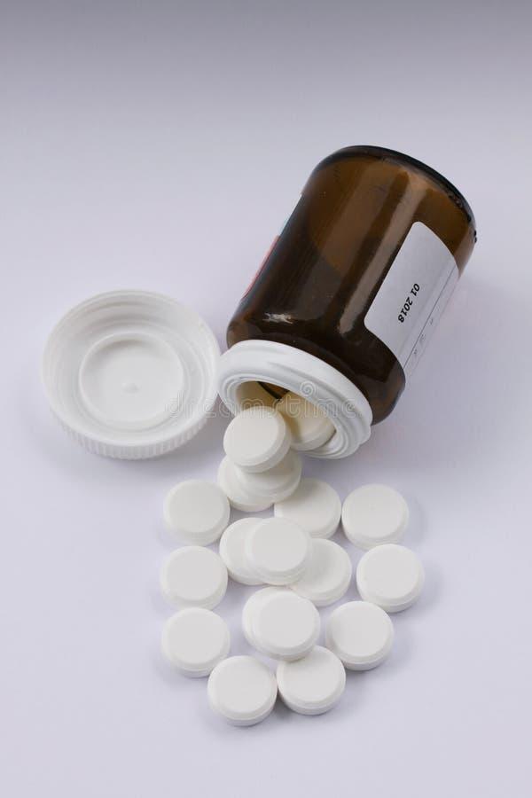 Vita preventivpillerar som spills från den stupade preventivpillerflaskan Preventivpillerar och medicinbehållare som ligger på vi arkivbilder