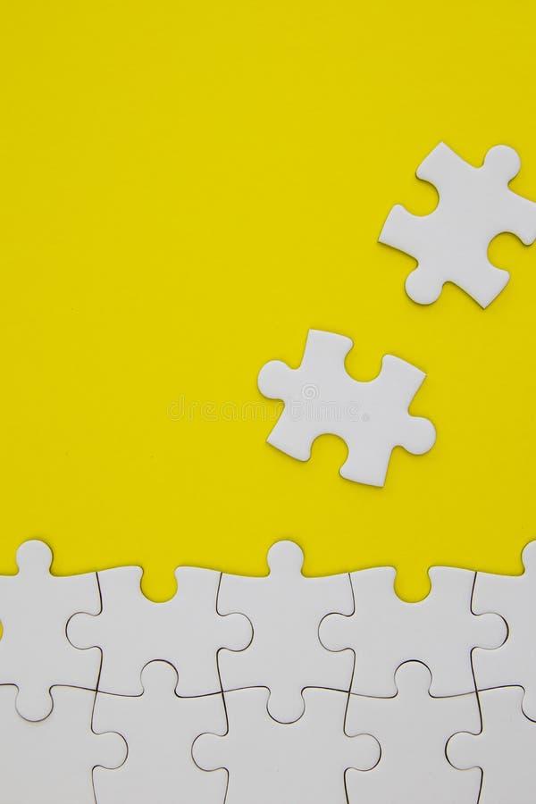 Vita pusselstycken på gul bakgrund med negativt utrymme royaltyfri foto