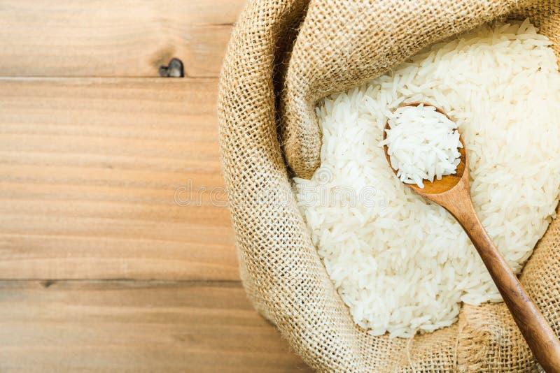 Vita rå thailändska jasminris i träsked i säckvävsäck på wood tabelltextur arkivfoto