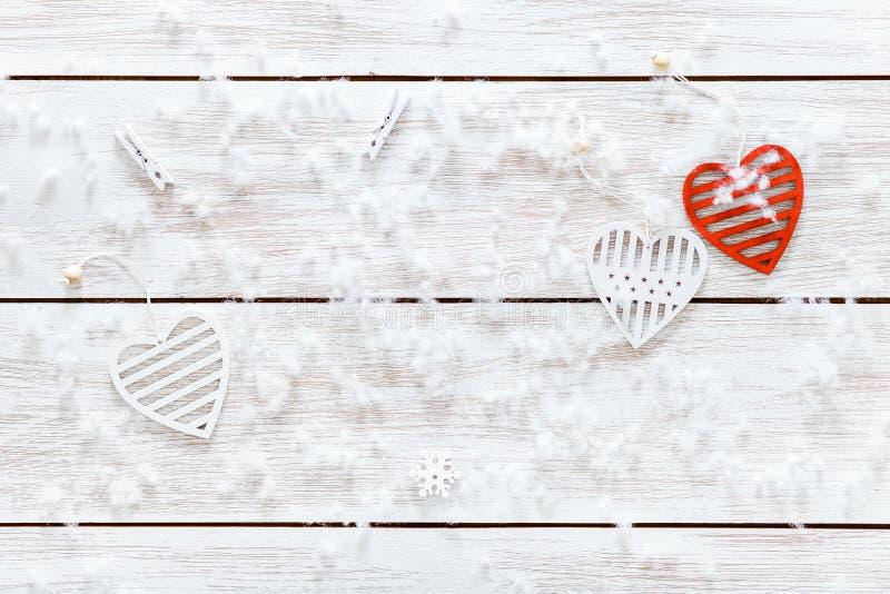 Vita röda hjärtor och snöflingor på trätabellen, romantiskt förälskelsekort, valentindagbakgrund, bästa sikt, kopieringsutrymme royaltyfri foto