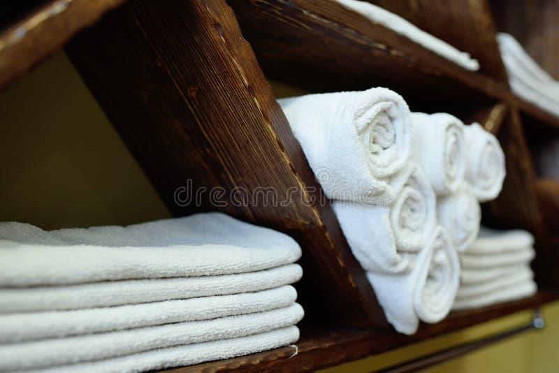 Vita rena handdukar trevligt vikta på en trähylla av en skönhetsalong eller frisersalong arkivbilder