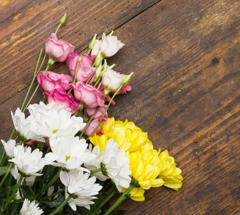 Vita rosa färg- och gulingblommor på träbakgrund royaltyfri foto