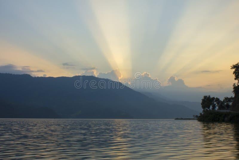 Vita rosa linjer av en solnedgång i den blåa himlen för afton över sjön och konturerna av berg royaltyfria foton