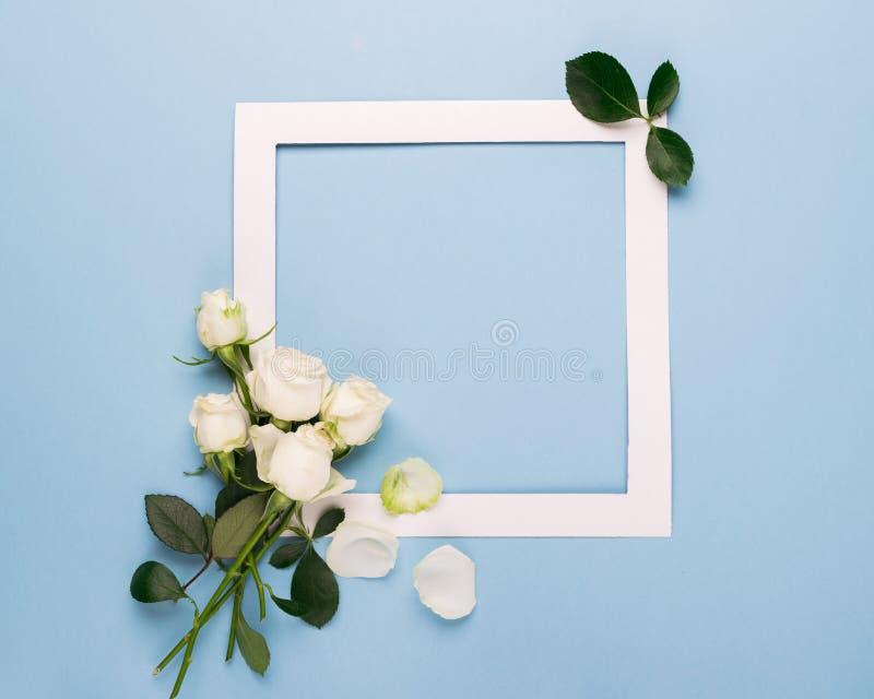 Vita rosor och en vitbokram dekoreras med nya sidor på en blå bakgrund Plan orientering kopiera avstånd celebratory royaltyfri fotografi