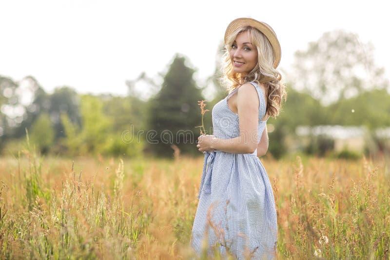 Vita rurale e rurale Camminando attraverso la giovane donna bionda del prato in un cappello summertime fotografie stock libere da diritti