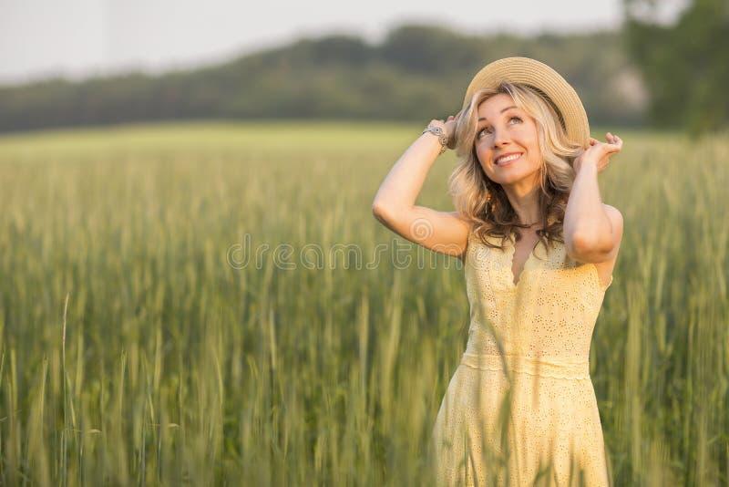 Vita rurale e rurale Camminando attraverso la giovane donna bionda del prato in un cappello summertime fotografia stock libera da diritti