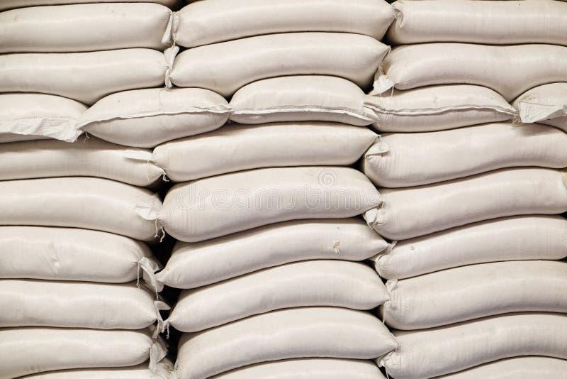 Vita säckar av ris i ris maler royaltyfria foton