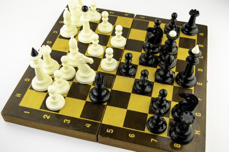 Vita schackstycken står på en schackbräde under en lek av schack, bästa sikt arkivbild