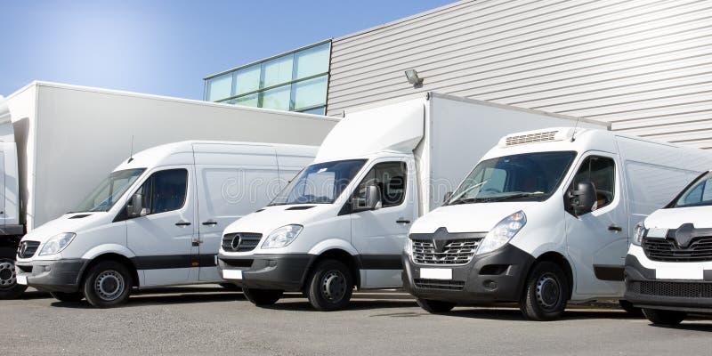 Vita skåpbilar för leverans i tjänste- skåpbillastbilar och bilar framme av ingången av en logistisk lagerfördelning royaltyfri bild