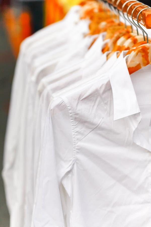 Vita skjortor för veck som i rad hänger på kuggen arkivbild