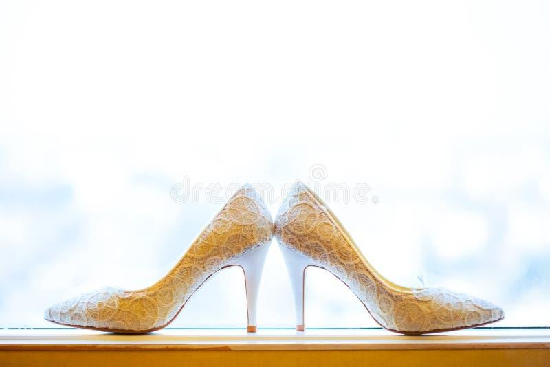 Vita skor av bröllopbruden med vit bakgrund arkivfoto