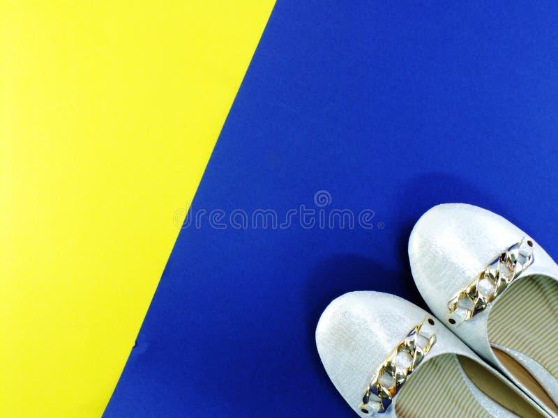 Vita skor för balettlägenhetdam på guling- och blåttbakgrund royaltyfri foto
