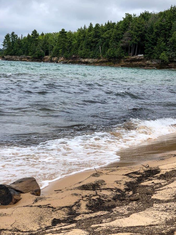 Vita skummande vågor som sköljas upp på stranden på den sandiga stranden fotografering för bildbyråer