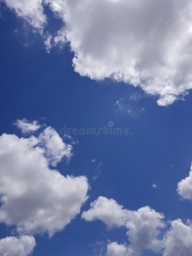 Vita stackmolnmoln mot en djupblå himmel gör perfekt som ett utbyte för en urtvättad himmel royaltyfri bild